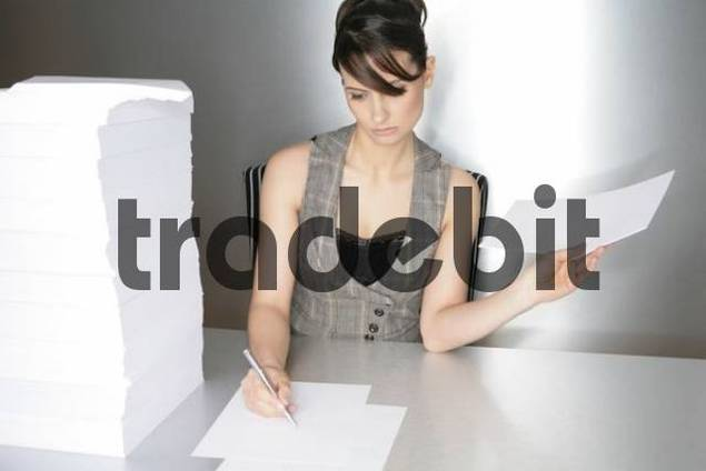 Businesswoman, aged 24, taking notes on a silver desktop