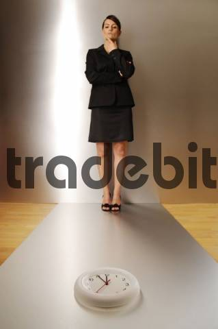 Businesswoman, aged 24, looking at a clock, focus is on the clock