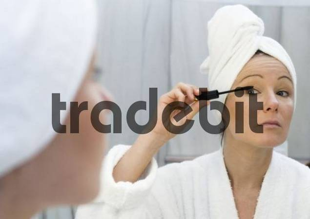 Young woman in bathroom applying, putting on mascara