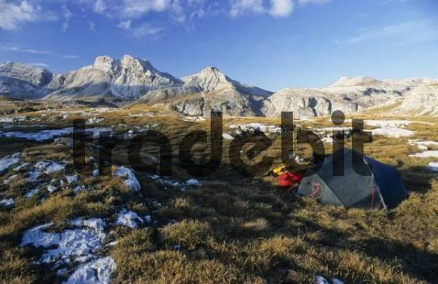 Green tent, yellow backpack, red down jacket and camping stove, autumnal mountain scenery, Groeden, Bolzano-Bozen, Italy, Europe