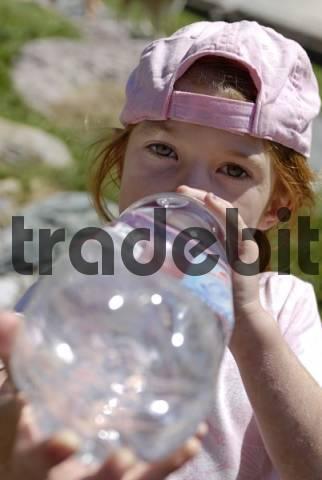 Girl drinking thurstily from a big water bottle, summer