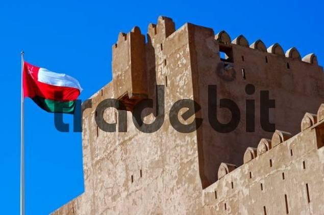 National flag of Oman fluttering in front of Jabrin Fort, Oman, Asia