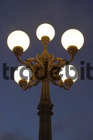 Historic street light at Lombardsbrücke shines into the night, Hamburg, Germany