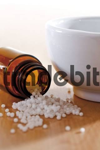 Apothecary bottle, homeopathic globules, mortar and pestle