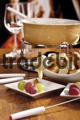 A cheese-dipped bread cube on a fondue fork in front of a fondue pan