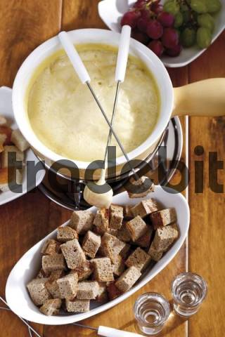 Cheese fondue, bread cubes on fondue forks and liquor