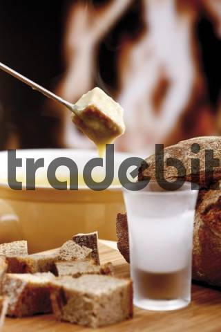 Ice cold liquor and a bread cube on a fondue fork being dipped in a cheese fondue in front of an open fireplace