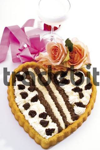 Cream Tart in the shape of a heart adorned with roses in front of a champagne glass and a ribbon