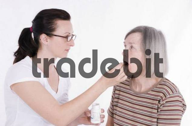 Elderly woman being administered pills from a nurse