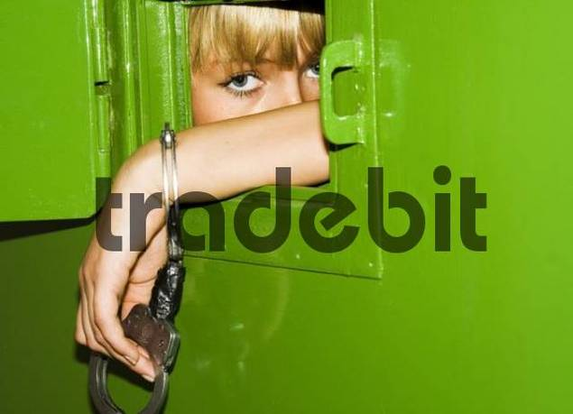Adolescent wearing handcuffs looking through the opening in a cell door, Berlin, Germany, Europe