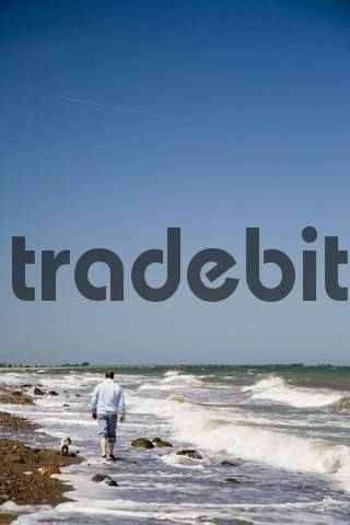 Man walking with a dog along a beach on the Baltic Sea