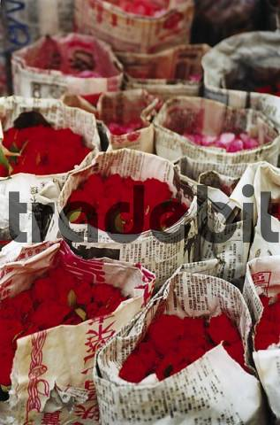 bunches of roses wrapped in newspapers