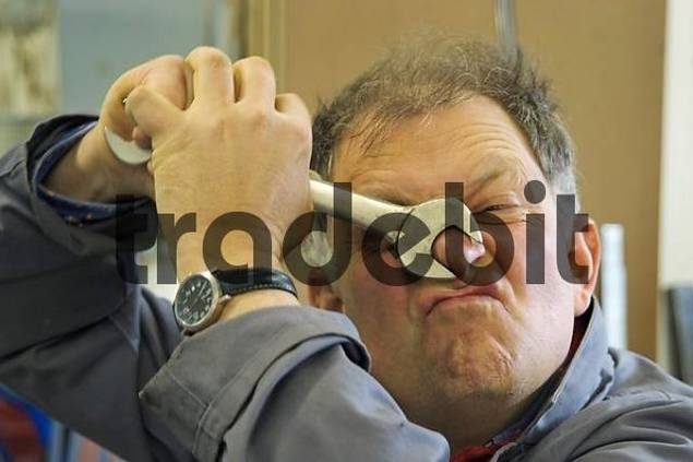 craftsman is clamping his nose with a screw wrench