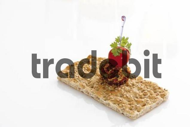 Crispbread with cream cheese ball and cocktail tomato