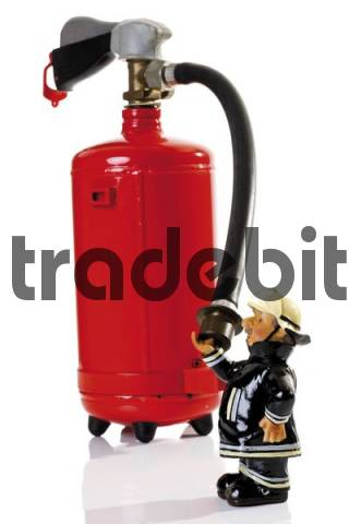 Decorative fireman figure standing in front of a fire extinguisher