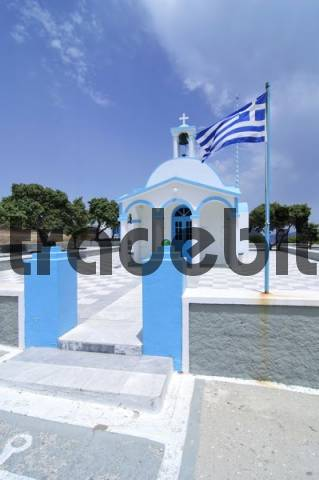 Blue and white chapel and a Greek flag blowing in the wind, Mykonos, Cyclades, Greece, Europe