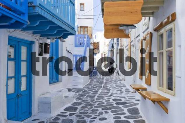 White houses in a narrow alley with colourful door frames and painted paving stones, Mykonos, Cyclades, Greece, Europe
