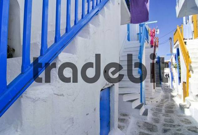 Characteristic colourful staircases and balustrades, painted floor made of stone and a motor scooter in a narrow alley in Mykonos, Cyclades, Greece, Europe
