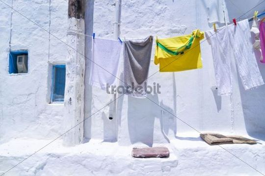 Washing hanging to dry on a washing line in front of a white house wall, Mykonos, Cyclades, Greece, Europe