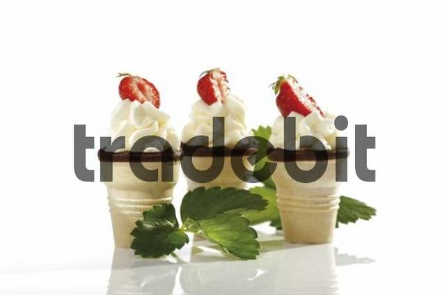 Wafer ice-cream cones with cream and strawberries