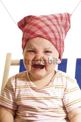Crying baby wearing a head scarf