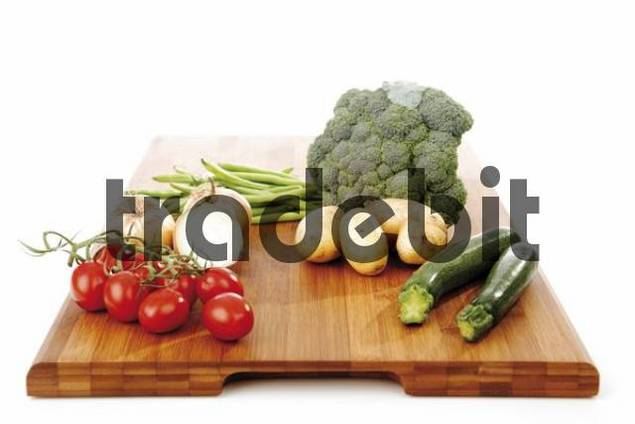 Mixed vegetables on a wooden chopping block, broccoli, zucchini, onions, potatoes, beans and tomatoes