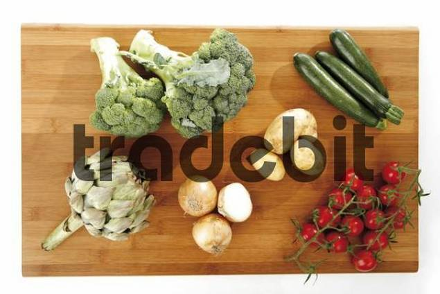 Mixed vegetables on a wooden chopping block, artichoke, broccoli, zucchini, onions, beans and tomatoes