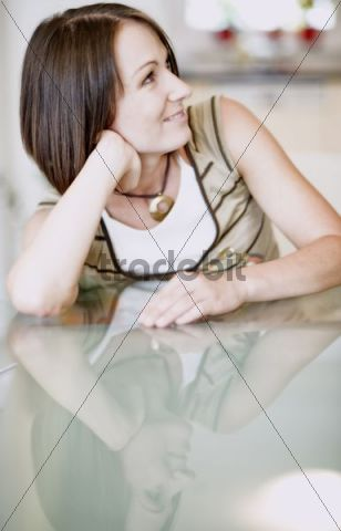 Young woman sitting at a table at home