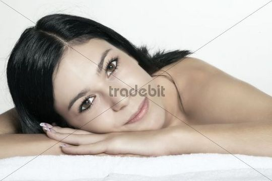 Dark haired young woman resting her head on her hands, portrait