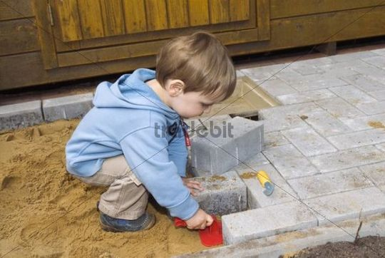 Little builder, a young boy, 20 months old, helping to pave a terrace
