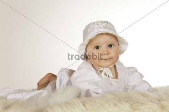 Baby, 6 months old, wearing a christening robe