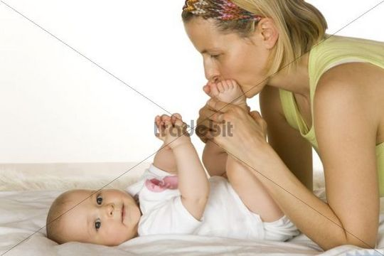 Mother cuddling with a baby, 6 months old, on a change table