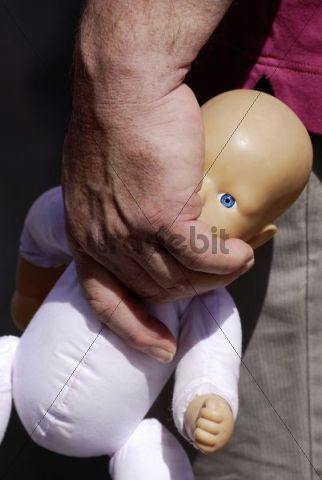 Meaty male hand carrying a doll by the neck, picture symbolizing violence against children, Emmendingen, Baden-Wuerttemberg, Germany