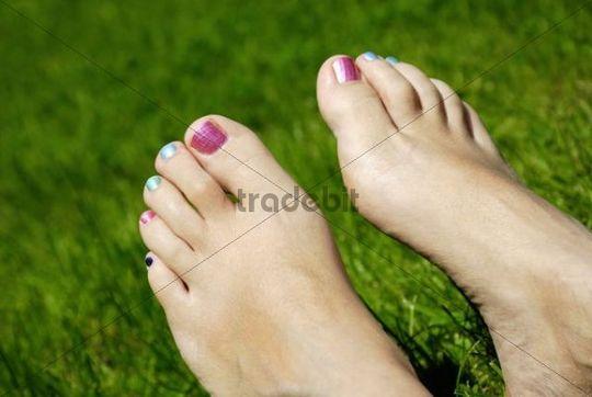 Nackte Frauenfüße im Gras, bunte Nägel
