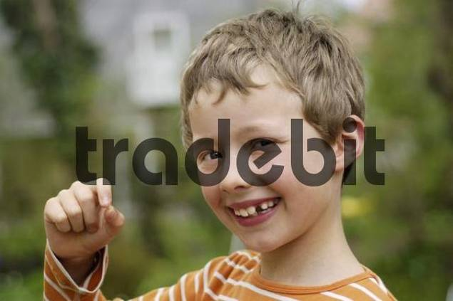 8 year old boy proudly holds his freshly fallen out milk tooth