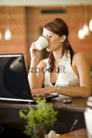 Young woman sitting in a coffee house at the counter, working on a laptop