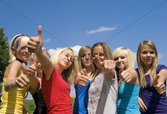 Optimisitic teenage girls giving the thumbs up