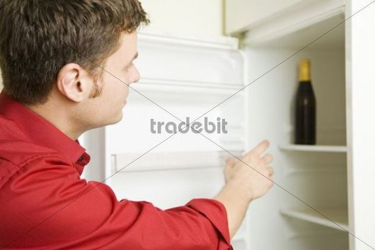 Man reaching for a bottle of beer in a fridge