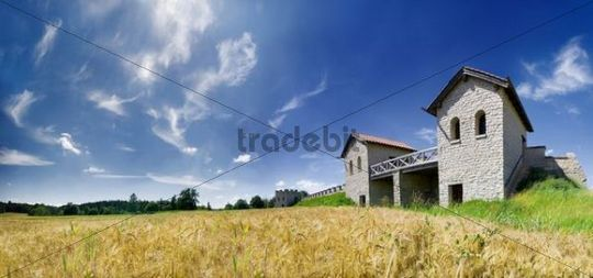 Wide angle shot of the Pfuenz Roman Fortress behind a barley field, in the Altmuehltal Nature Park, Eichstaett, Baveria, Germany, Europe