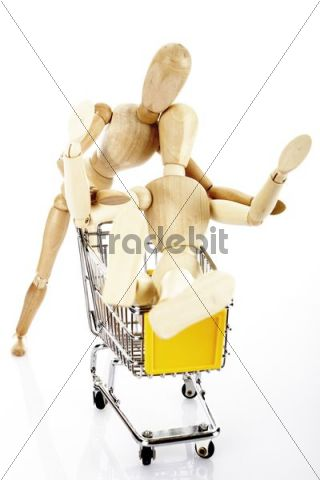 Two wooden jointed figures with a shopping trolley