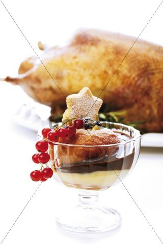 Baked apple with chocolate sauce and custard, out-of-focus roast christmas goose in the back