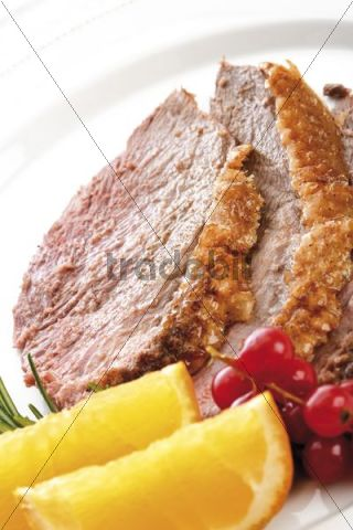 Two slices of goose-breast, red-currants and orange slices