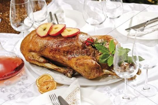 Roast goose with apple rings on a festively decorated table