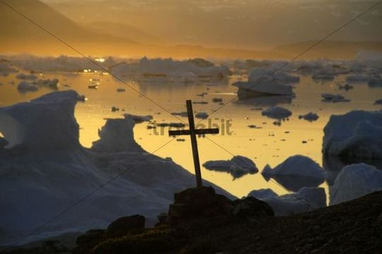 Christian cross in front of icebergs in the orange evening light, Parnakajiit, Sermilik Fjord, East Greenland, Arctic