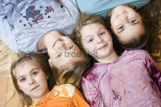 Group of four little girls lying on the floor, from the left 6, 11, 9 and 10 years old, birds-eye view