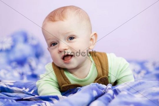 Smiling baby boy, 7 months old, on a bed