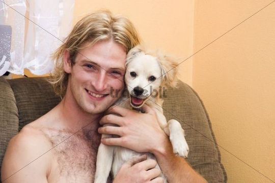 Smiling blond man, 25 years, and his smiling dog