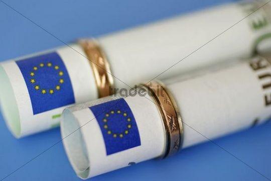 Euro bank notes and wedding rings