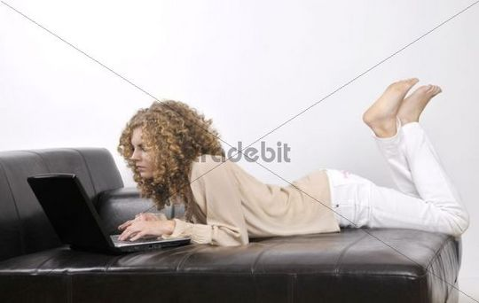 Young woman, 20, lying down with a laptop, curly hair