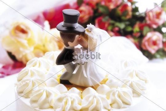 Wedding cake topped with a bride and groom figurine